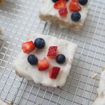 All-American Sugar Cookie Bars, the perfect patriotic dessert! Light cookie bars topped with homemade icing and fresh strawberries and blueberries. Celebrate American with this festive dessert! sugar cookie | cookie recipe | sugar cookie bar | cookie bars | july 4th dessert | july 4th recipe | independence day dessert | red white blue dessert | patriotic dessert | fruit dessert | strawberry dessert | blueberry dessert