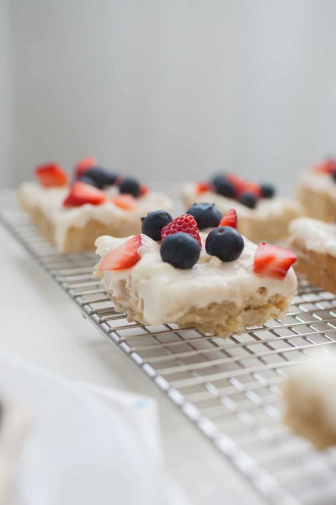 All-American Sugar Cookie Bars, the perfect patriotic dessert! Light cookie bars topped with homemade icing and fresh strawberries and blueberries. Celebrate American with this festive dessert! sugar cookie   cookie recipe   sugar cookie bar   cookie bars   july 4th dessert   july 4th recipe   independence day dessert   red white blue dessert   patriotic dessert   fruit dessert   strawberry dessert   blueberry dessert
