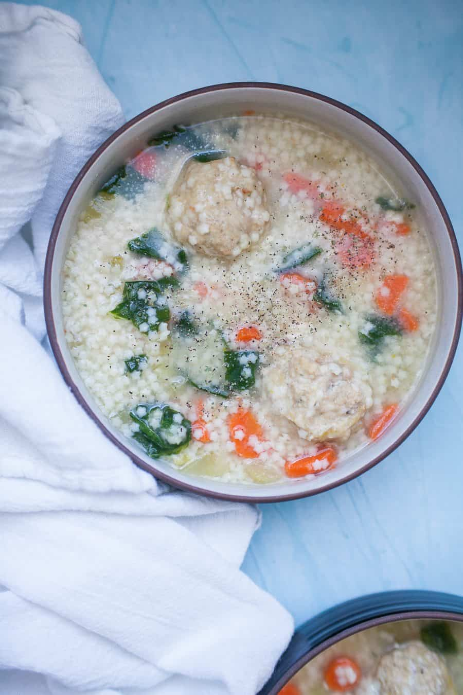 Shallow bowl of homemade Italian wedding soup with carrots, celery, onions, spinach, pasta and meatballs.