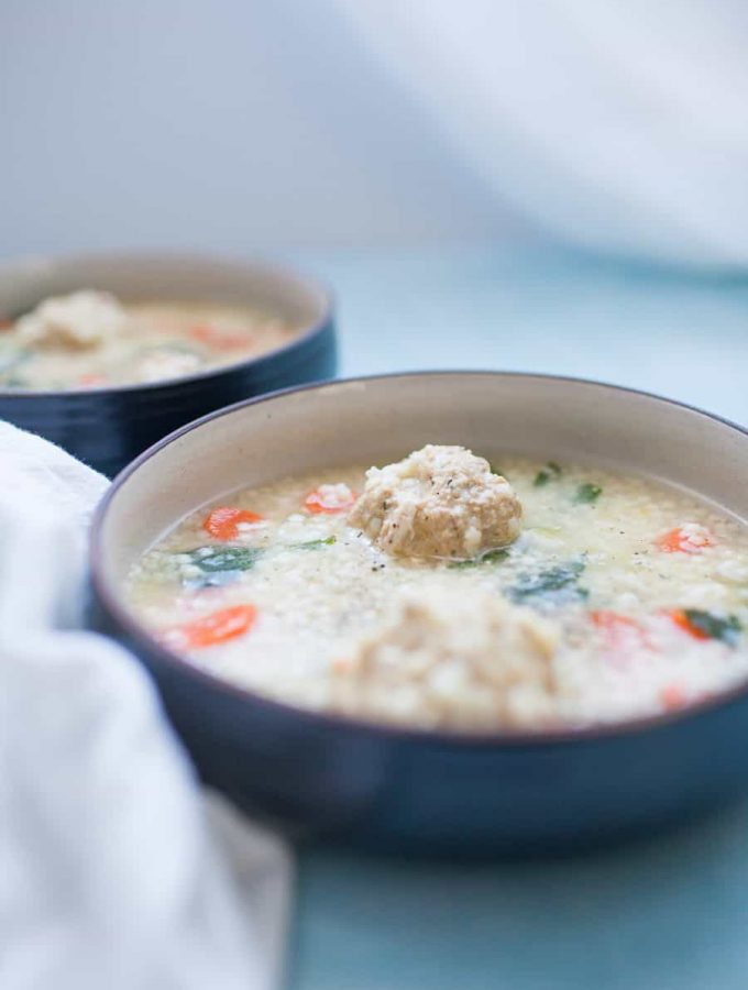 Shallow bowl of homemade Italian wedding soup with carrots, celery, onions, spinach, pasta and meatballs. Light blue background. White flour sack, kitchen towel on board.