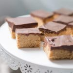 No Bake Peanut Butter Chocolate Bars are incredibly easy to make ahead of time and serve for any event! These indulgent, creamy treats are sure to disappear quickly and you'll be wishing you had more! These no bake dessert bars are made with just a handful of ingredients, but make no mistake they are not lacking in any sort of delicious flavor. A crunchy peanut butter and graham cracker crust is topped with smooth chocolate and creates the perfect peanut butter and chocolate combination that everyone will drool over.