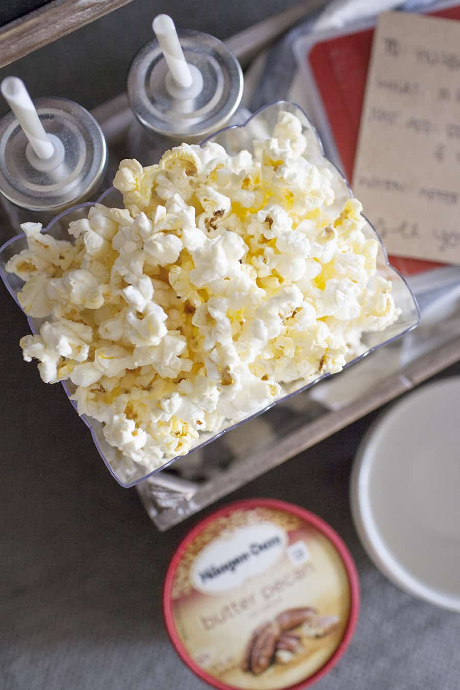 "This movie night date crate is the perfect way to have a date night at home while your little one is asleep! Share some popcorn, a movie and Häagen Dazs® ice cream in these DIY ""yours and mine"" ice cream bowls for a quiet date night at home."
