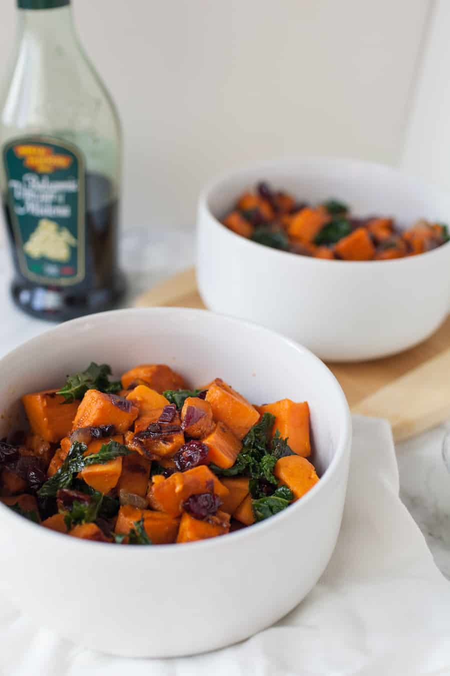 In need of a quick but delicious side dish for dinner? This sweet potato and kale sauté is perfectly delicious and easy to make. The sweet potatoes are the star of this show, but the red onions, cranberries, kale and a splash of balsamic vinegar make this dish robust in flavor! easy side dish | side dish ideas | sweet potatoes | kale | red onions | onions | cranberries | balsamic vinegar