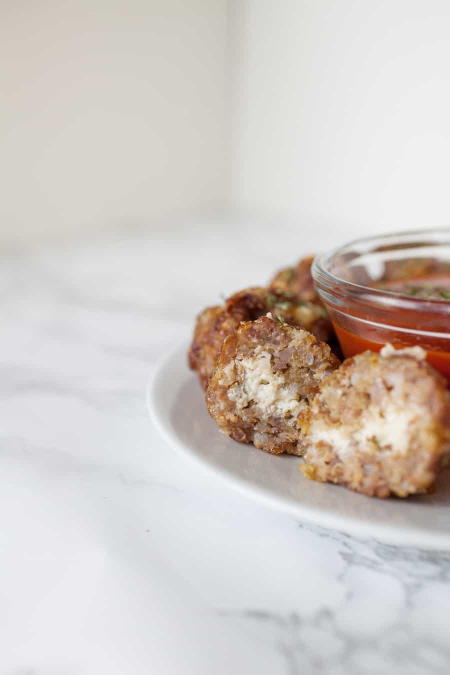 Looking for a quick and easy appetizer for the Big Game? These ricotta stuffed sausage meatballs are so easy to make. Your football friends will go wild for these quick baked ricotta stuffed sausage meatballs at your Big Game party! party food | meatballs from scratch | meatball recipes | meatballs | appetizer recipes | superbowl party food | football food