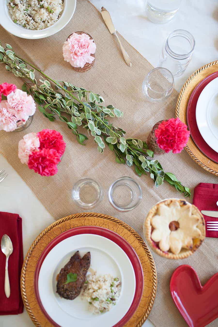 Looking for an easy date night in for Valentine's Day this year? This easy tablescape is the perfect way to wow your sweetheart this year. Plan a gorgeous tablescape with stacked plates of different colors, mixed metals and fresh carnations for a stunning look! valentines day ideas | date night at home | date night | valentines day dinner | valentines day table | valentine's day decor | valentines ideas | steak dinner ideas