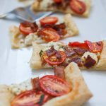 This Tomato Bacon Goat Cheese Puff Pastry Appetizer is the perfect pre-dinner snack when you're hosting friends and family! It's so quick to throw together and enjoy while dinner finishes cooking. A simple frozen puff pastry topped with  crispy bacon pieces, dollops of goat cheese and sliced grape tomatoes makes a quick appetizer that everyone will enjoy!
