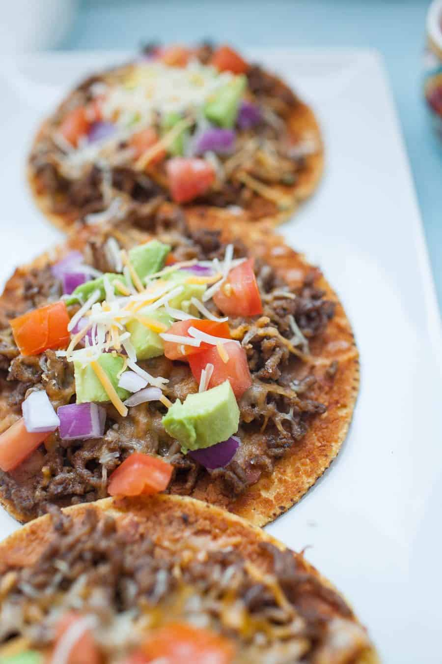 Easy ground beef tostadas are the perfect dinner for busy weeknights! They're quick to make and can be customized a ton of ways to be your perfect flavor combination! Start with a flat, crunchy corn tortilla and add your toppings like beans, ground beef, tomatoes, avocado and cheese for a flavorful, quick dinner.