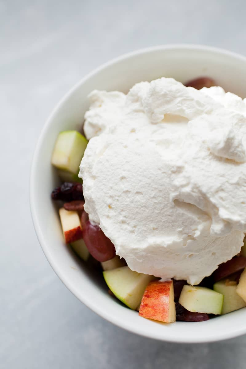 Creamy fruit salad with a heaping pile of whipped cream on top.