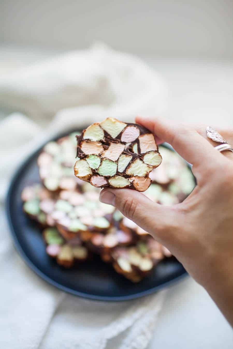 A female hand holding a cookie with colored marshmallows and chocolate.