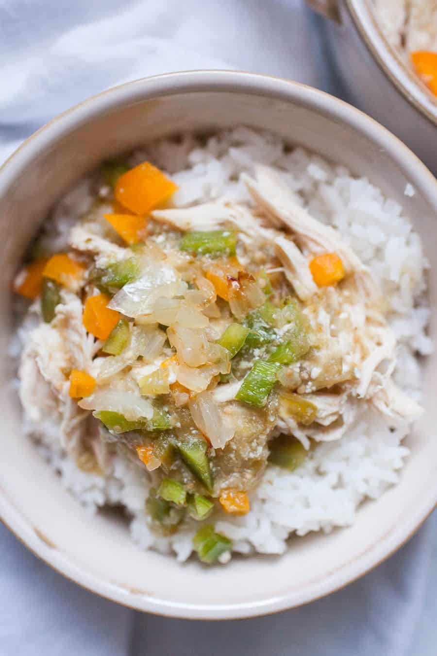 This five ingredient Salsa Verde Chicken is an easy weeknight slow cooker meal the whole family will love! It's made with jarred salsa verde, chicken, bell peppers, onions and rice and it's ready in a matter without even thinking about it.