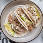These Slow Cooker Salsa Verde Pulled Pork Tacos are the perfect dish for lunch, dinner, or just because they're so yummy! They're made with slow cooker Salsa Verde Pulled Pork, cotija cheese, avocado, white rice and a little extra salsa verde poured on for good measure. You don't need an occasion to indulge with these tacos!