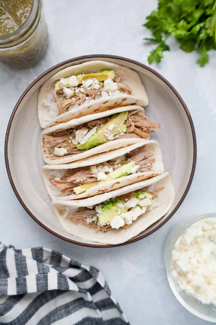 These Salsa Verde Pulled Pork tacos are the perfect dish for lunch, dinner, or just because they're so yummy! They're made with slow cooker Salsa Verde Pulled Pork, cotija cheese, avocado and a little extra salsa verde poured on for good measure. You don't need an occasion to indulge with these tacos!
