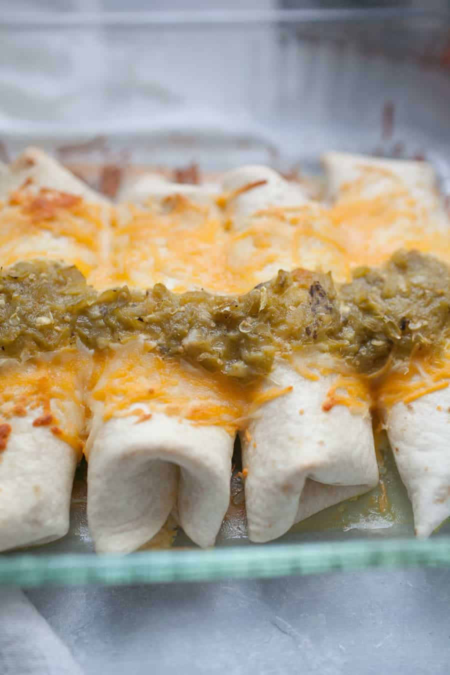 Sour Cream Chicken Enchiladas are the perfect weeknight dinner that will gather your family around the table. These enchiladas are made with flour tortillas, instead of traditionally used corn tortillas, and are stuffed with shredded chicken mixed with cream of chicken soup, sour cream, and cheese. The whole dish is topped with cheese and spicy green chile sauce! It's packed with flavor and the perfect dish for your family!