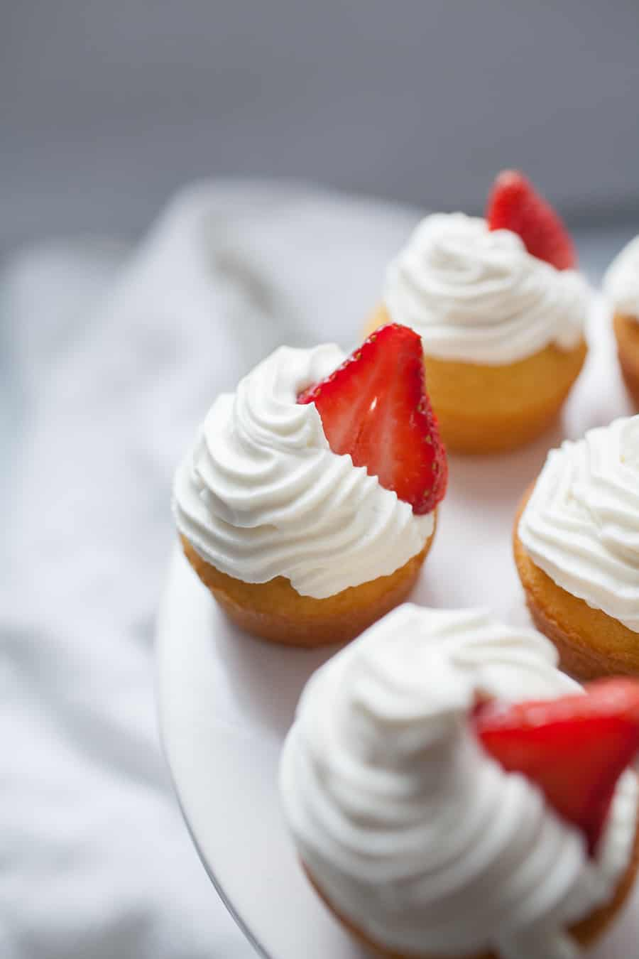 Strawberry Shortcake Cupcakes with Whipped Cream Frostingare the perfect dessert for any occasion. These cupcakes are light and fluffy and bring the experience of eating strawberry shortcake into a cupcake! Spruce up a boxed cake mix with a few add ins and your own homemade whipped cream icing that tastes just like the real thing. Top with a slice of fresh strawberry and you're ready to share these cupcakes over a cup of coffee with friends!