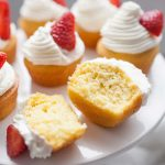 Strawberry Shortcake Cupcakes are the perfect dessert for any occasion. These cupcakes are light and fluffy and bring the experience of eating strawberry shortcake into a cupcake! Spruce up a boxed cake mix with a few add ins and your own homemade whipped cream icing that tastes just like the real thing. Top with a slice of fresh strawberry and you're ready to share these cupcakes over a cup of coffee with friends!