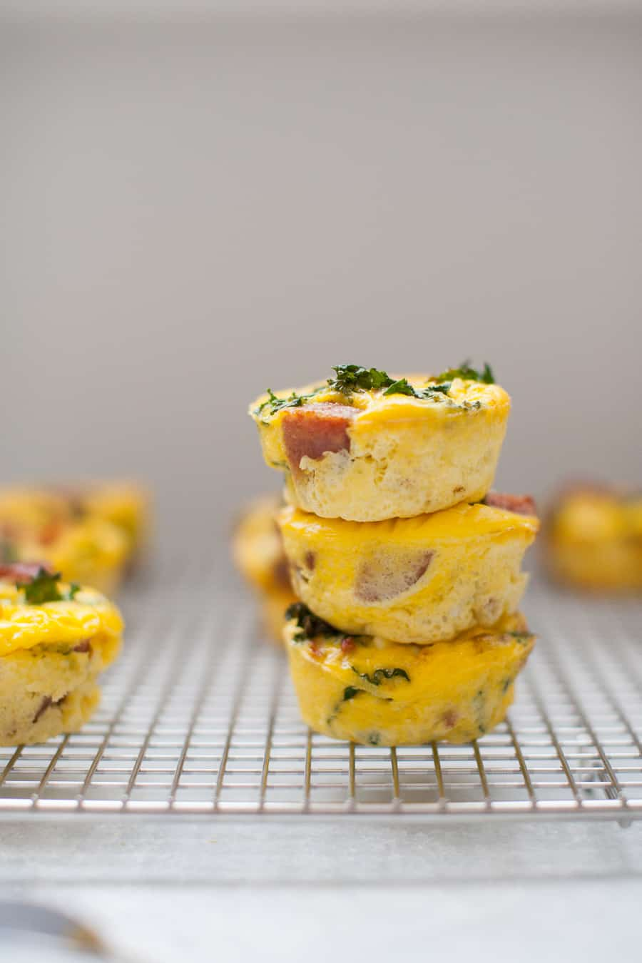 Make Ahead Egg Muffins are a perfect solution for making breakfast ahead of time for the week, to take to work or for brunch! Made with smoked sausage, kale, sundried tomatoes and feta, these egg muffins are small but packed with flavor.