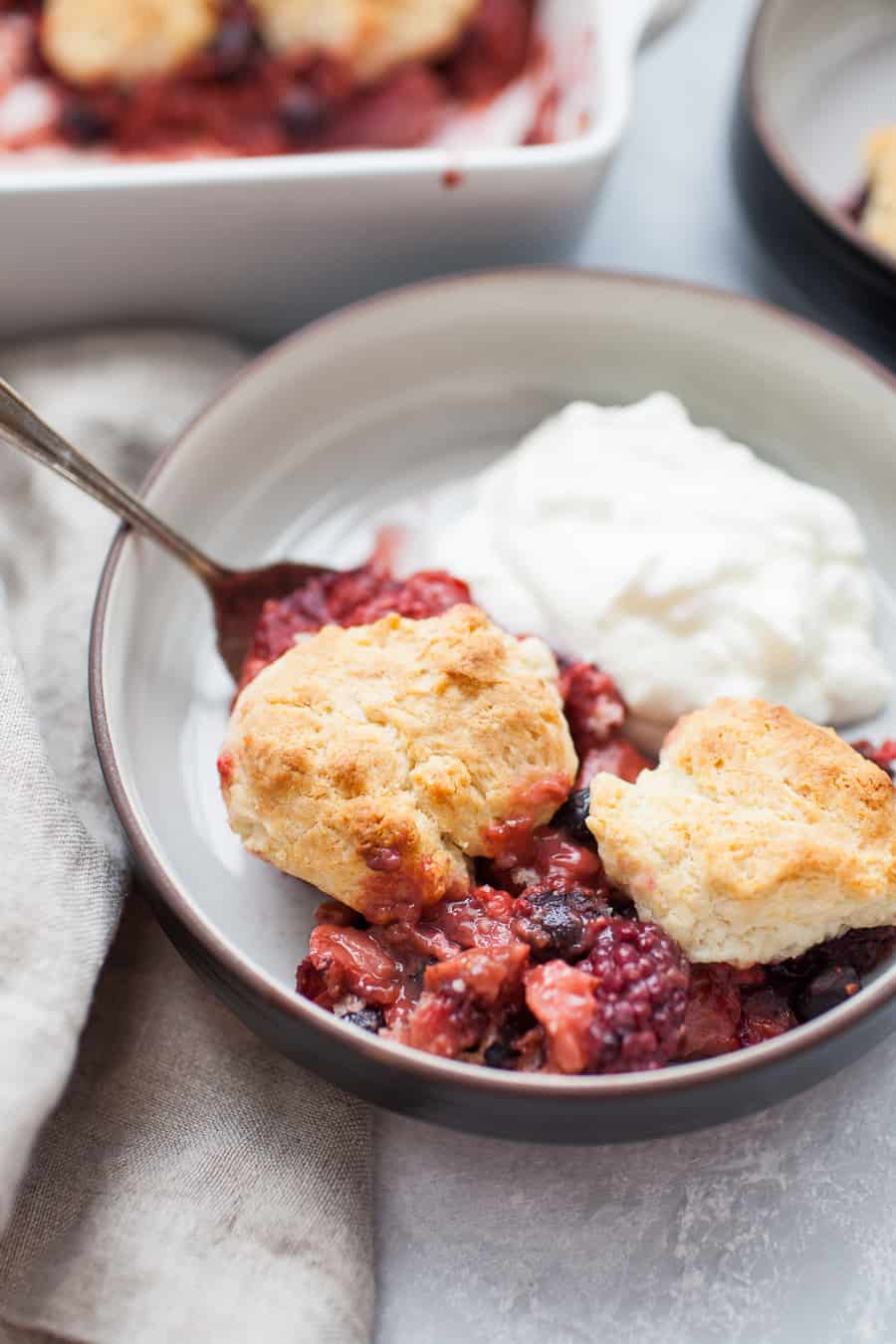 Close up of black shallow bowl with triple berry cobbler and yogurt in it. Antique spoon is sitting in bowl. Blueberries, strawberries and blackberries are visible in the cobbler. There is a scoop of yogurt in the back of the bowl and a white square baking dish and second bowl of cobbler are blurred in the background of the photo.