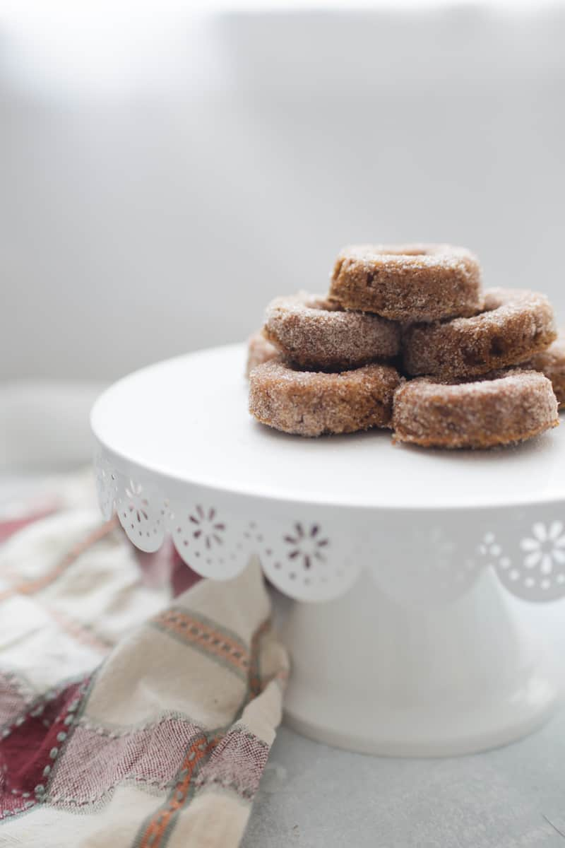 Stack of mini pumpkin donuts on a white cake stand.