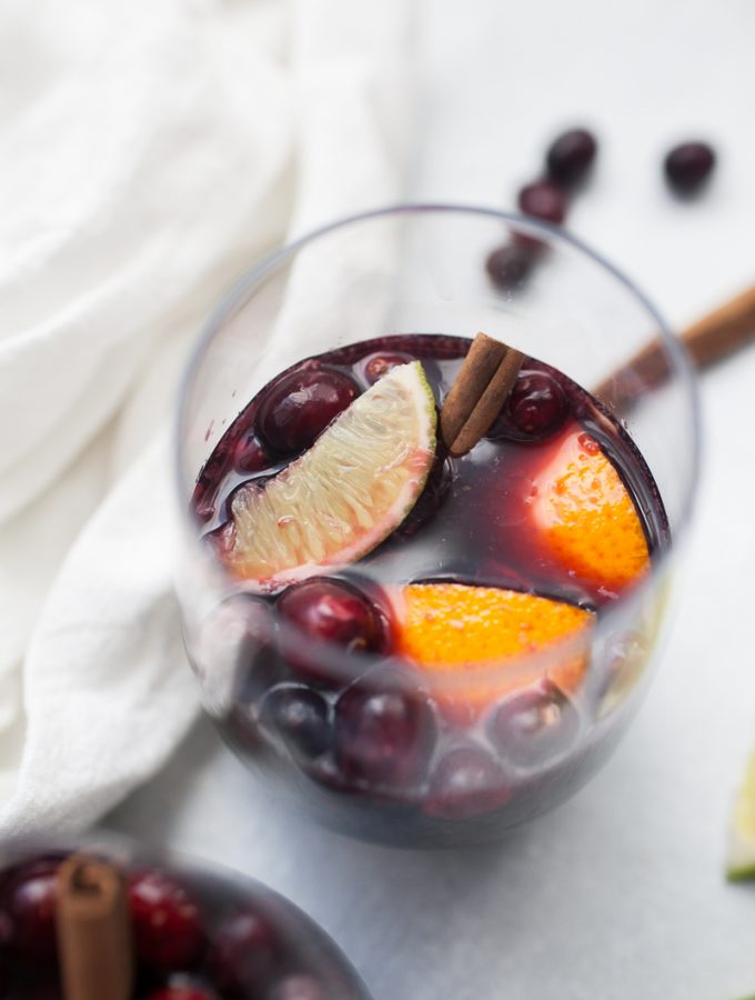 Glass of sangria made with lime, orange and cranberry.