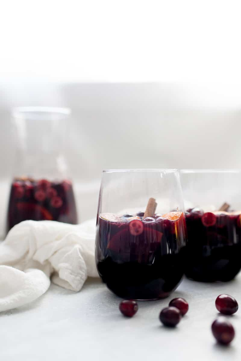 Two stemless wine glasses in front of a wine carafe filled with red sangria.
