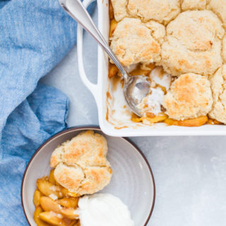 Square baking dish with peach cobbler.