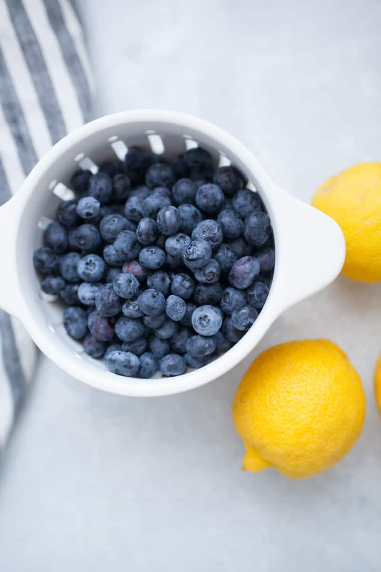 White colander of blueberries with lemons.