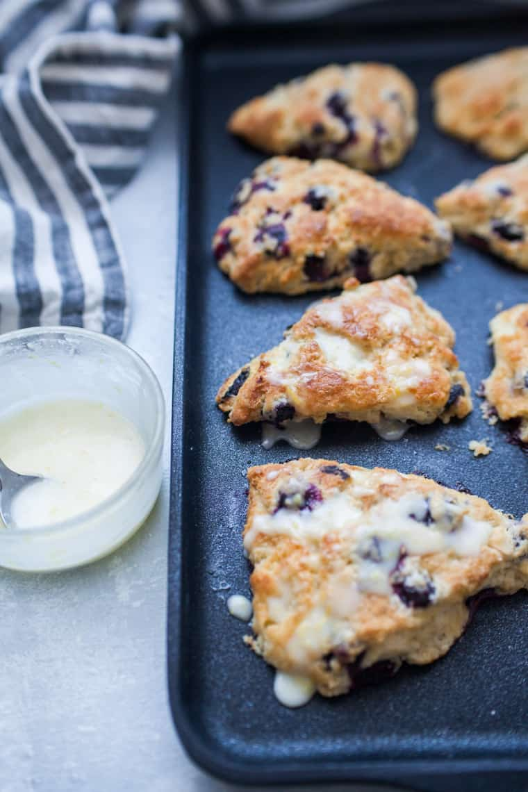 Blueberry scones on a black baking pan with a striped linen and bowl of lemon glaze.